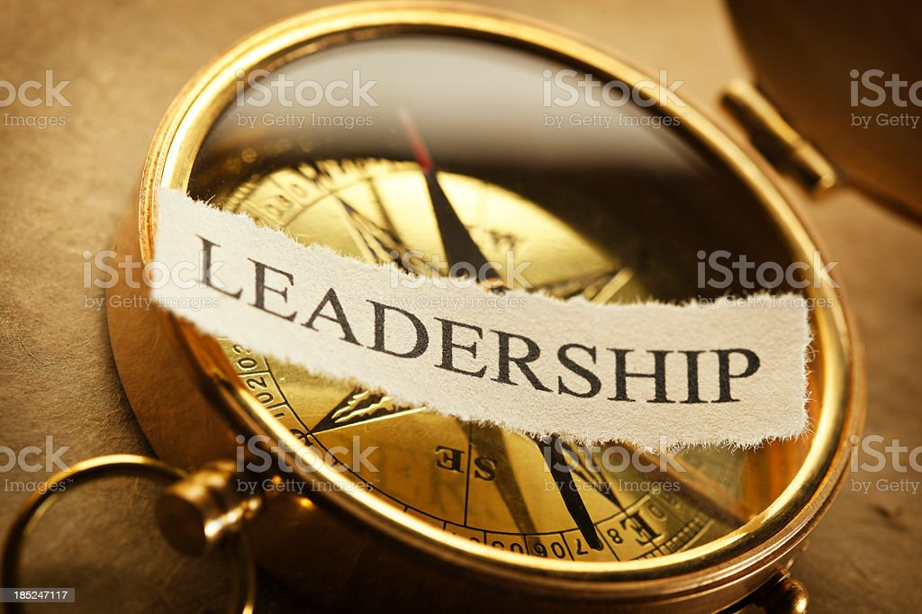 The word leadership on a golden compass stock photo