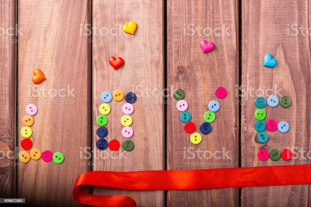 the word love formed from multi-colored buttons stock photo