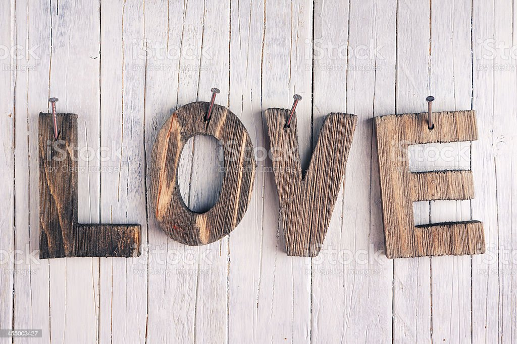 The word 'love' in wooden letters on a rustic background stock photo