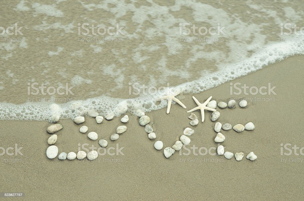 The word love written at the beach stock photo