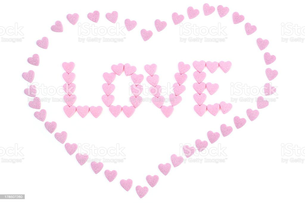 The word 'love' written with small candy hearts royalty-free stock photo