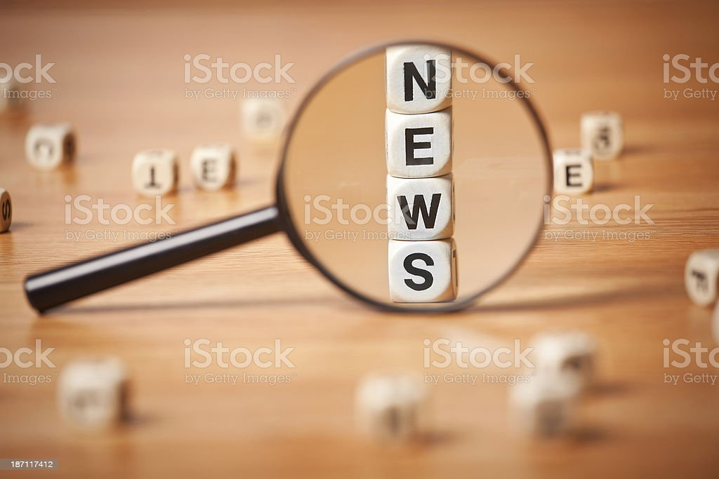The Word NEWS Spelled In Letter Cubes Though Magnifying Glass royalty-free stock photo