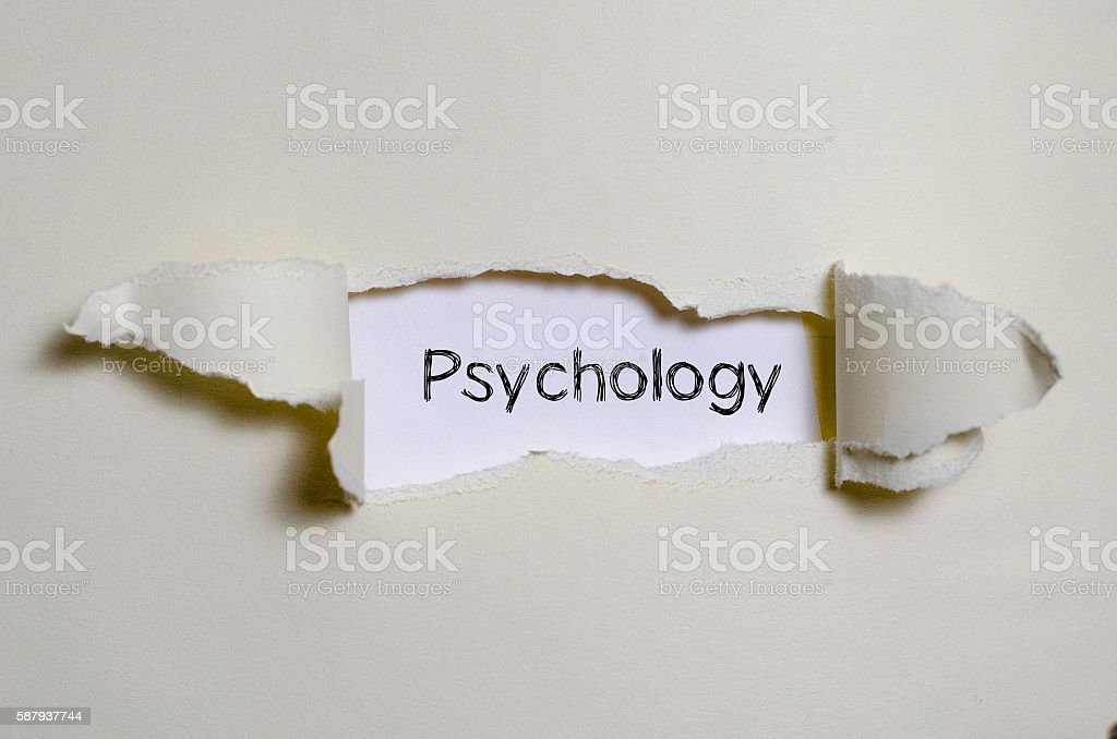 The word psychology appearing behind torn paper. stock photo