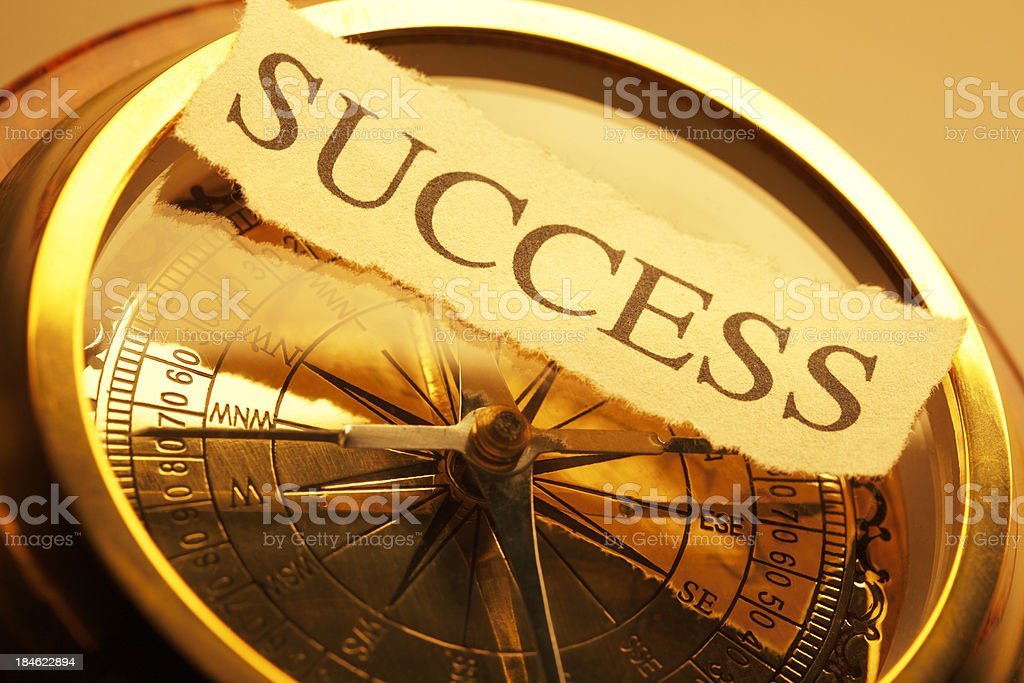 The word success on a golden compass royalty-free stock photo
