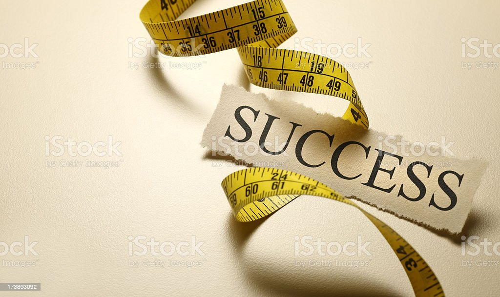The word success on top of coiled tape measure stock photo