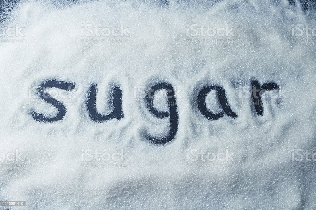 The word sugar written in a pile of white sugar stock photo