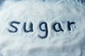 The word sugar written in a pile of white sugar