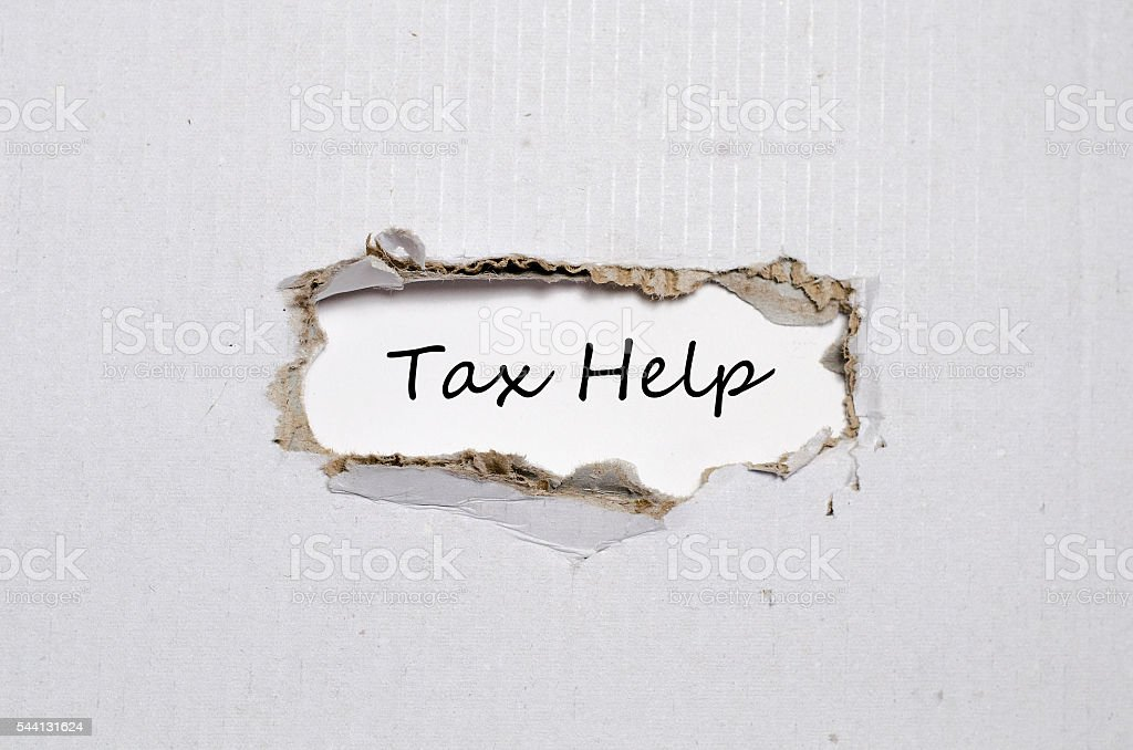 The word tax help appearing behind torn paper. stock photo