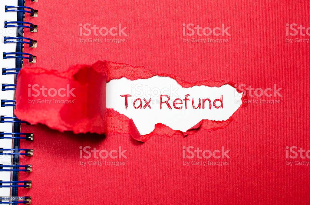 The word tax refund appearing behind torn paper. stock photo