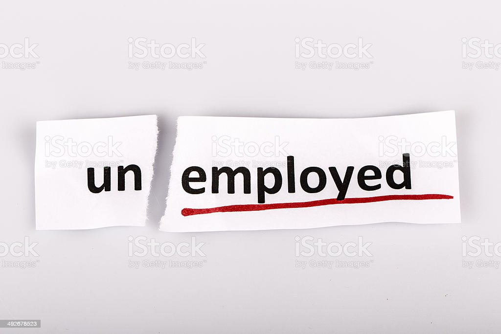 The word unemployed changed to employed on torn paper stock photo