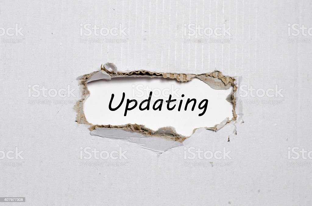 The word updating appearing behind torn paper stock photo