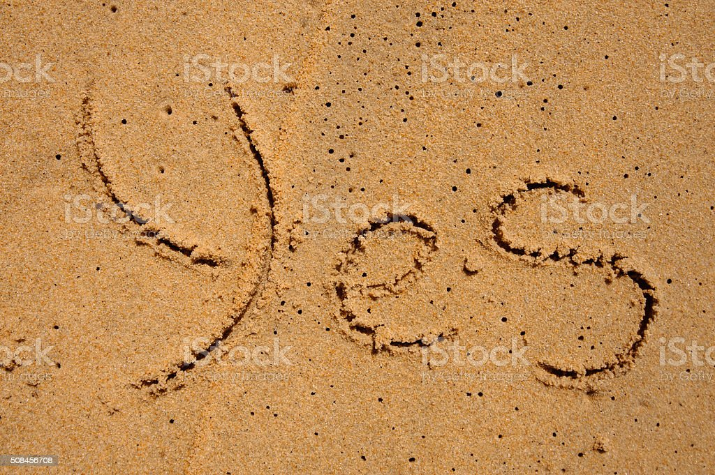 The word yes is carved on the sand stock photo