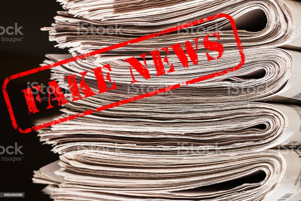 The words Fake News in red text on a newspapers stock photo