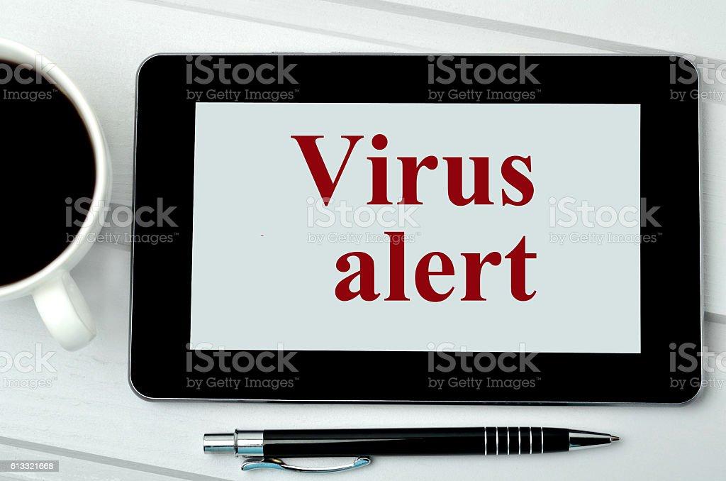 The words Virus alert on digital tablet stock photo