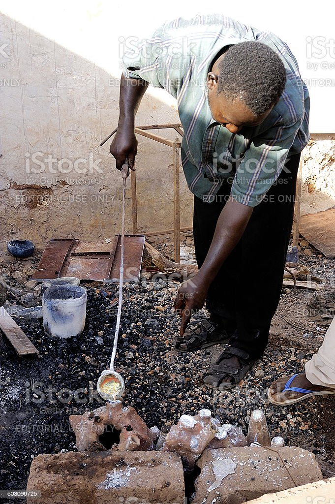 Ouagadougou, Burkina Faso – November 18, 2010 : The bronzier pays a...