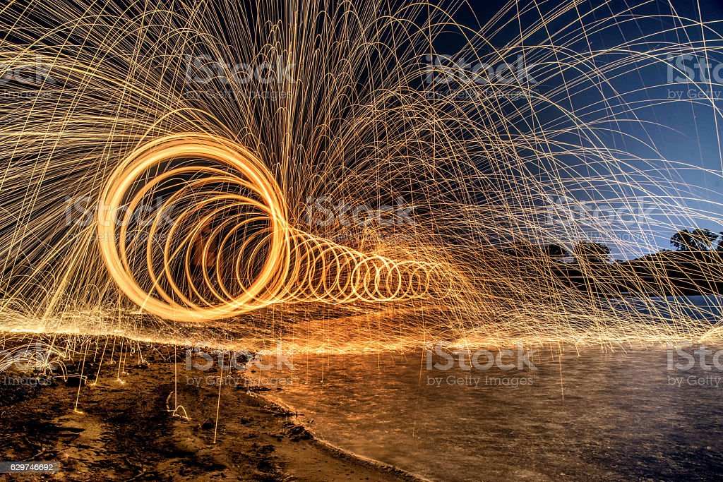 The work of glowing sparks from spinning steel wool.. stock photo