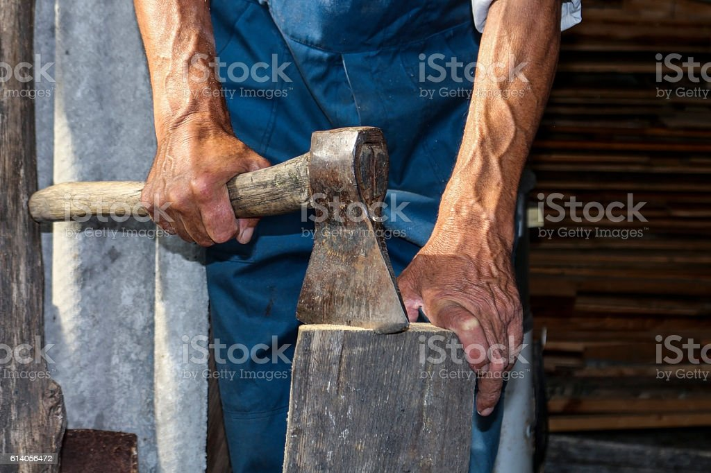 The worker, a man with an ax chopping firewood stock photo