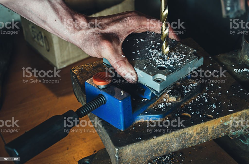 The worker in his garage works on a drilling machine. In the frame, a person's hands stock photo