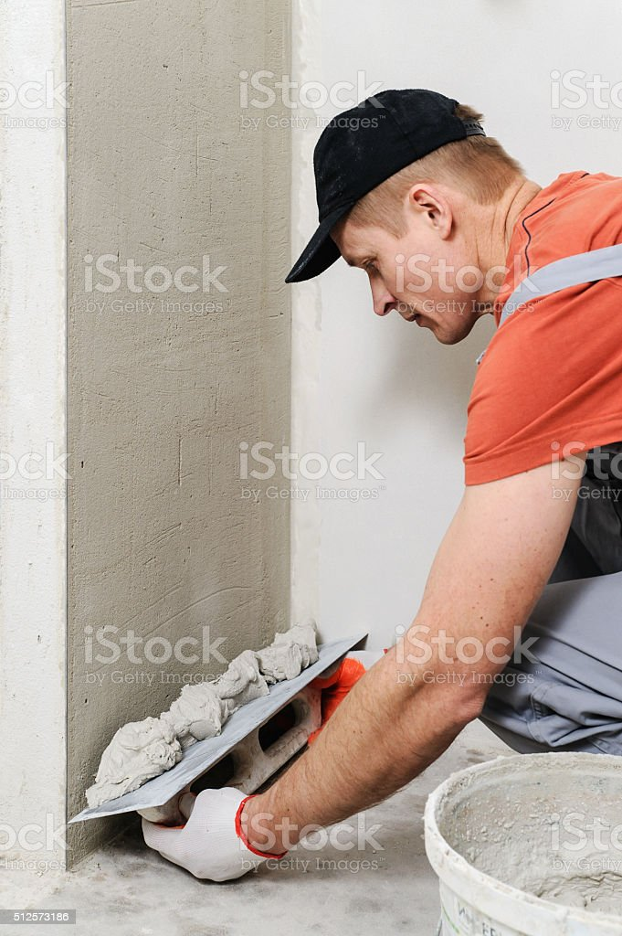The worker puts the stucco on the wall stock photo