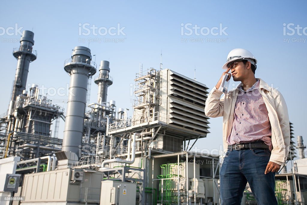 The worker standing in front of power plant station stock photo