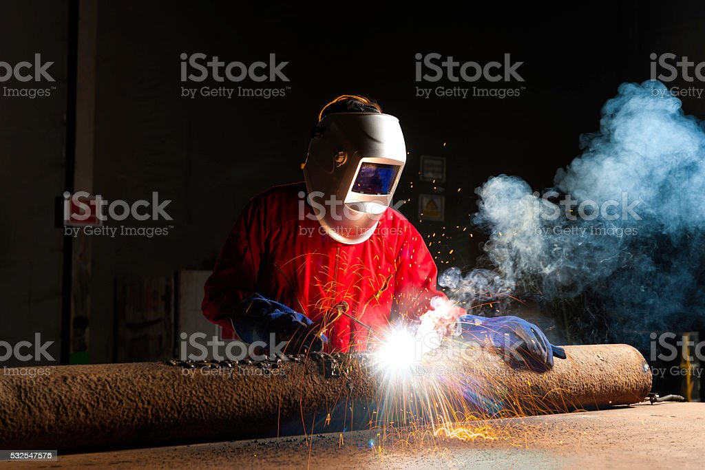 The worker welding metal in manufacturing plant, sparks flying stock photo