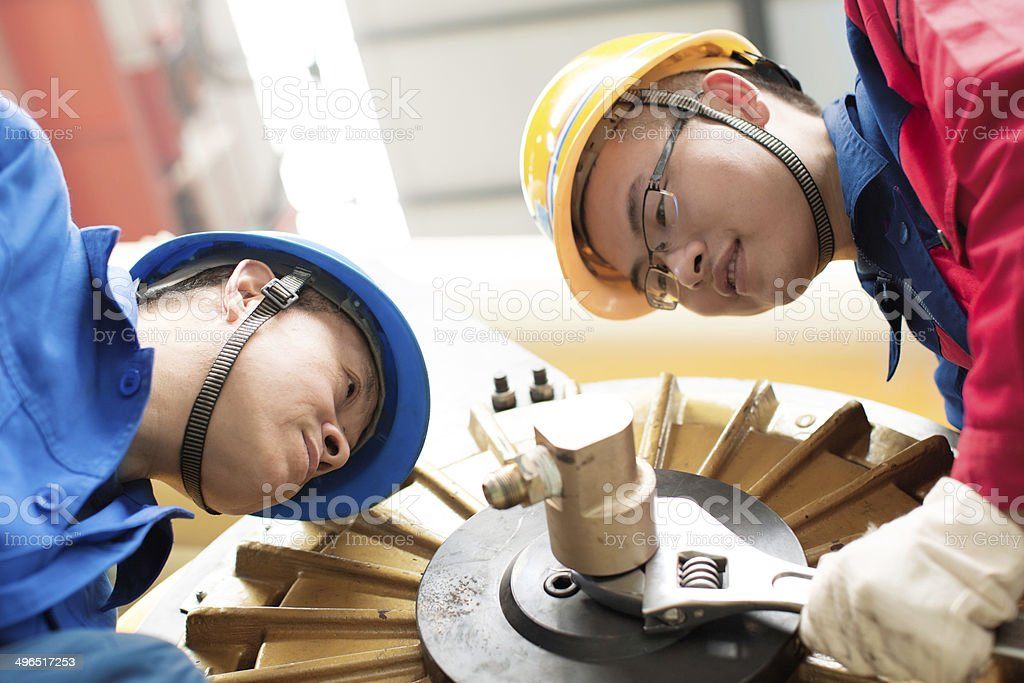The workers are installing a machine in a factory stock photo