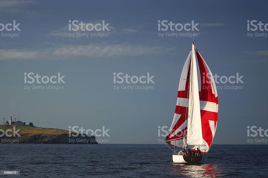 The Yacht with a red sail near island. royalty-free stock photo