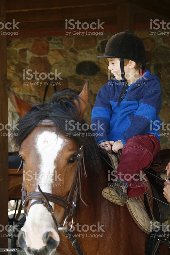 The young boy rides on a horse stock photo