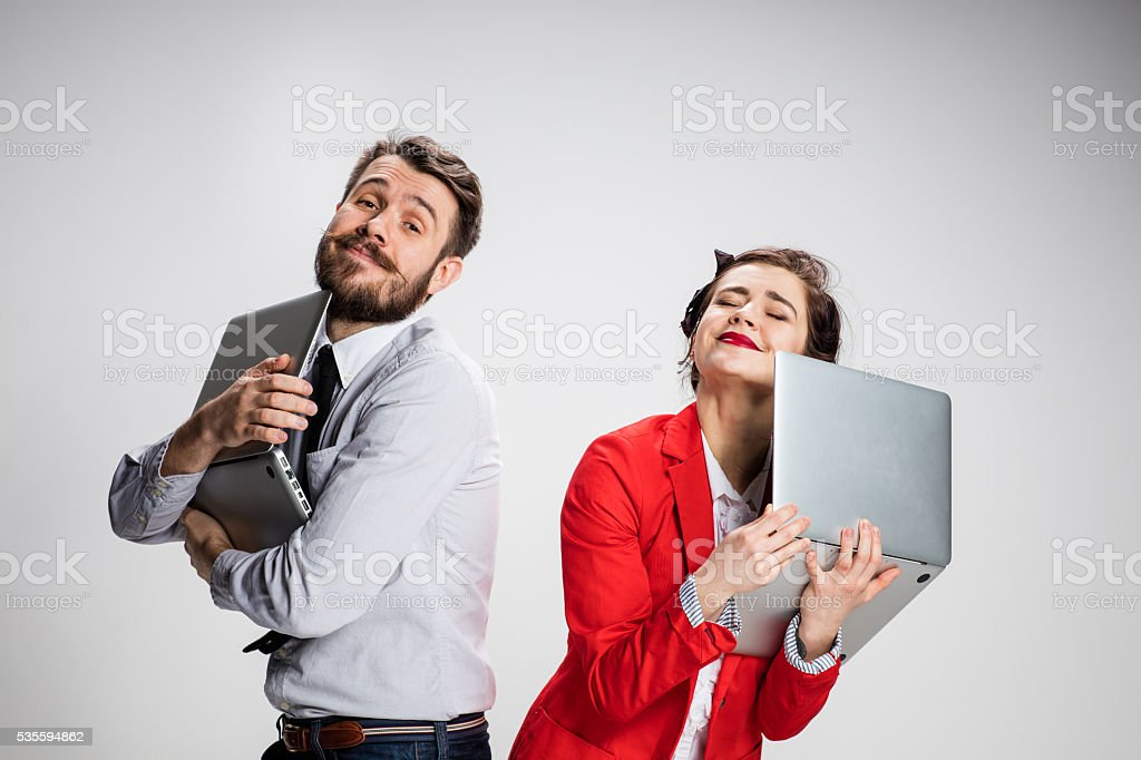 The young businessman and businesswoman with laptops on gray background stock photo