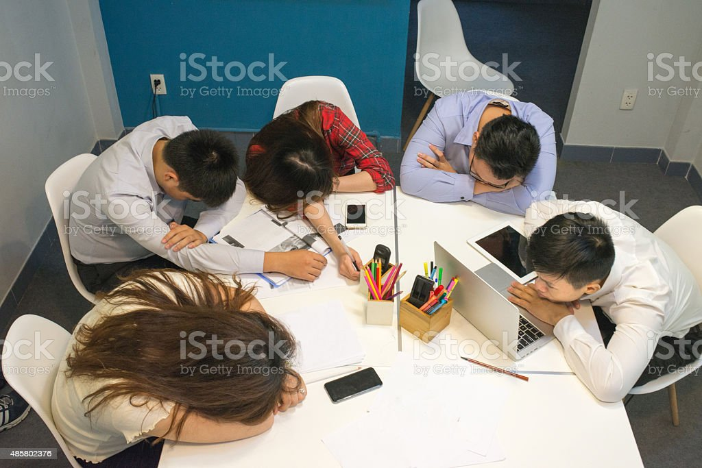 The young businessman try to work while his workmate sleeping stock photo