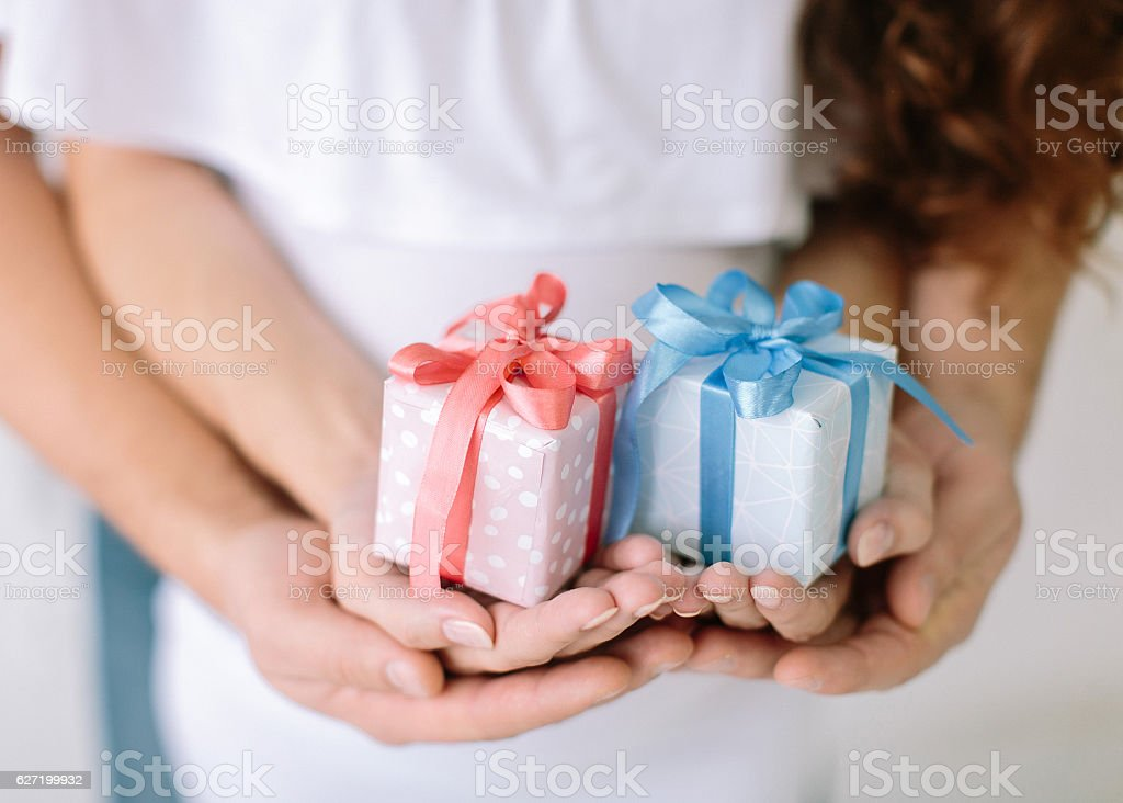 the young family holds a pink and blue gift surprise stock photo
