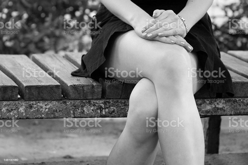 a jovem garota sozinha sentada sobre um banco. foto royalty-free