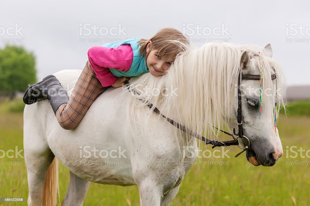 The young girl lies on the white horse back stock photo