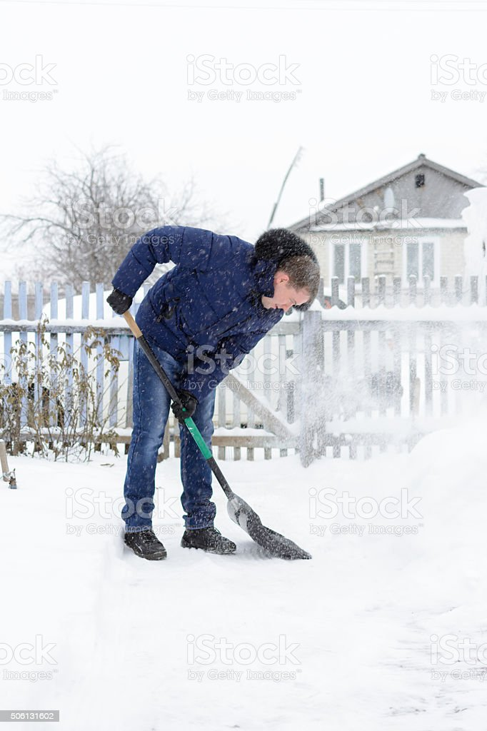 The young man clears snow in the yard stock photo