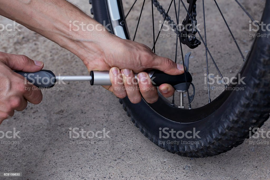 The young man inflates bicycle wheel stock photo