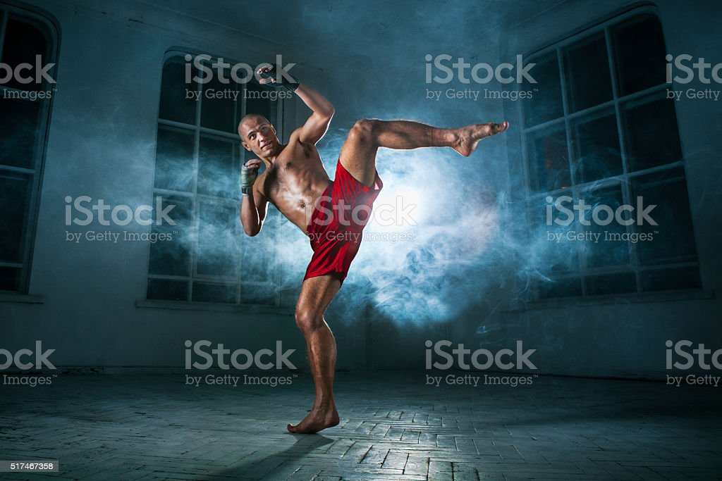 The young man kickboxing in blue smoke stock photo