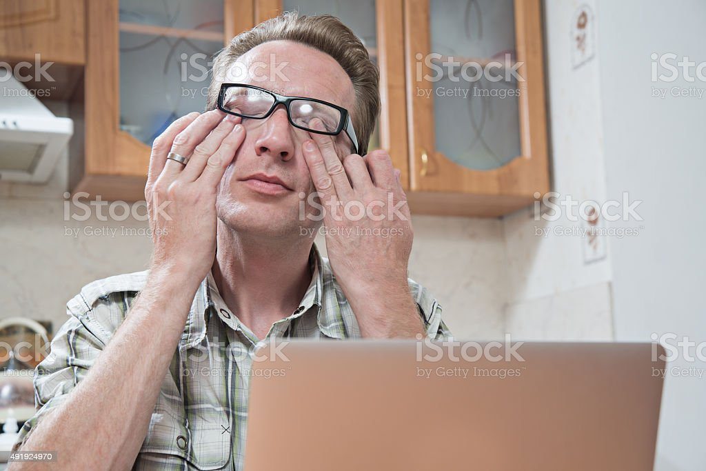 the young man rubs tired eyes stock photo