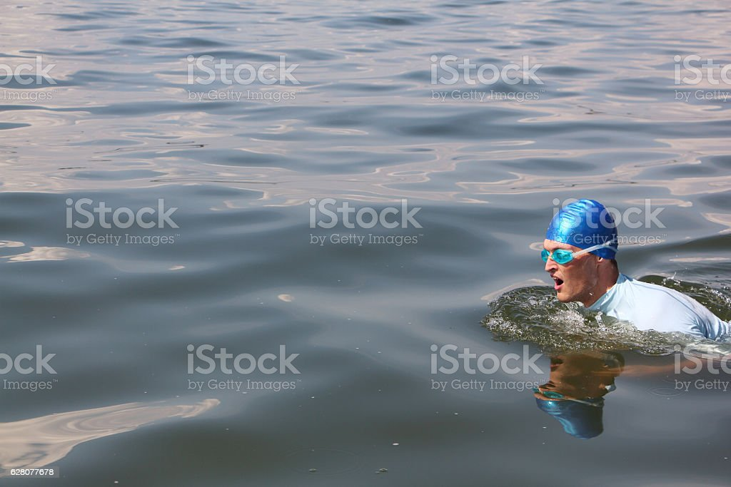 The young man swimming in the river stock photo