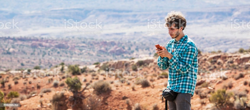 The young man, traveler, filming the Salt Valley in Arches National Park with smartphone. XXXL stitched panorama. stock photo