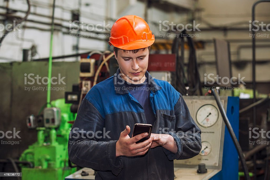 The young man working at the old factory on installation stock photo