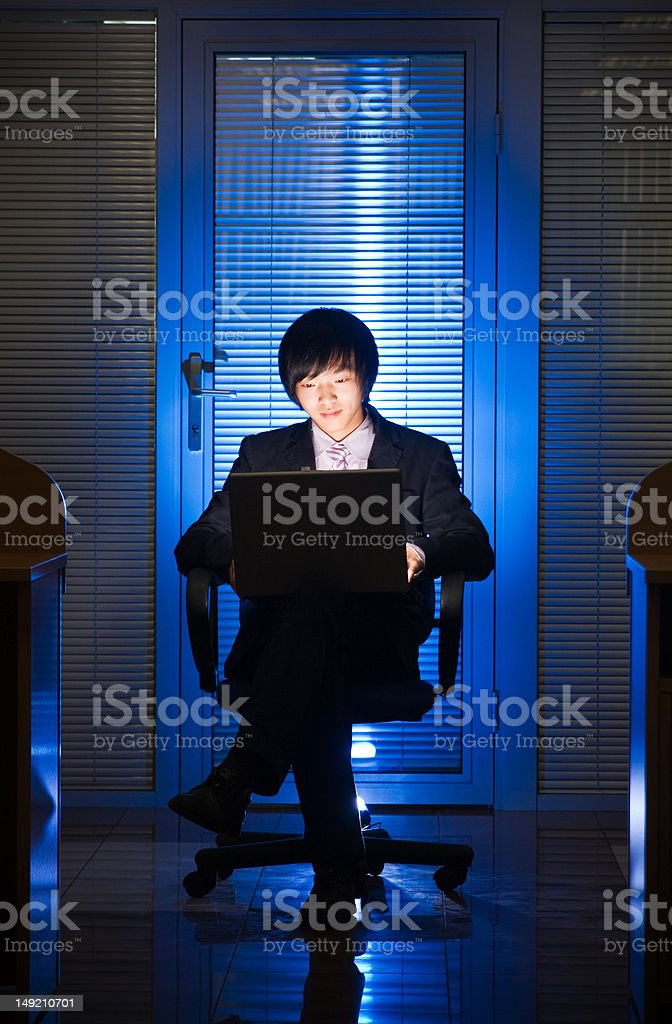 The young man works behind a laptop royalty-free stock photo