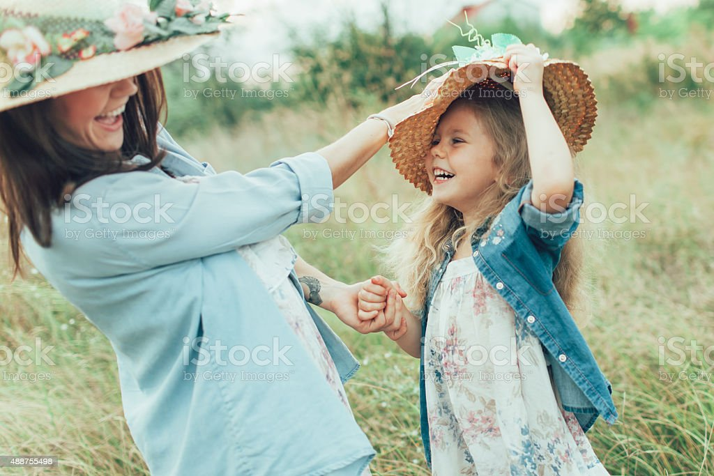 The young mother and daughter on green grass background stock photo
