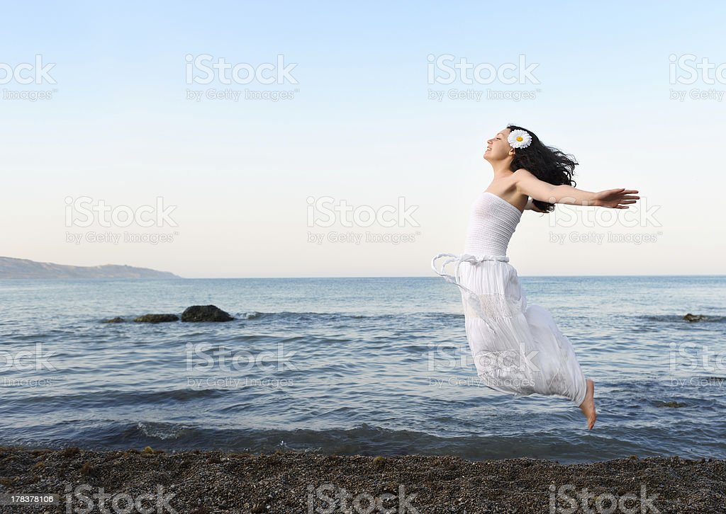 The young woman jumps on seacoast royalty-free stock photo