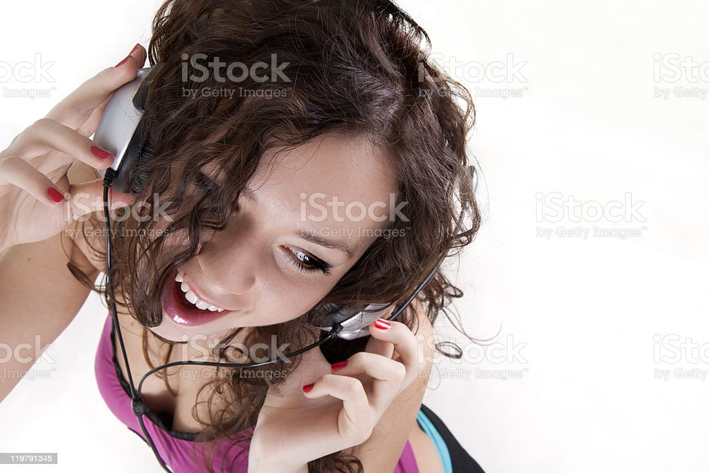 The young woman listens to music in ear-phones royalty-free stock photo