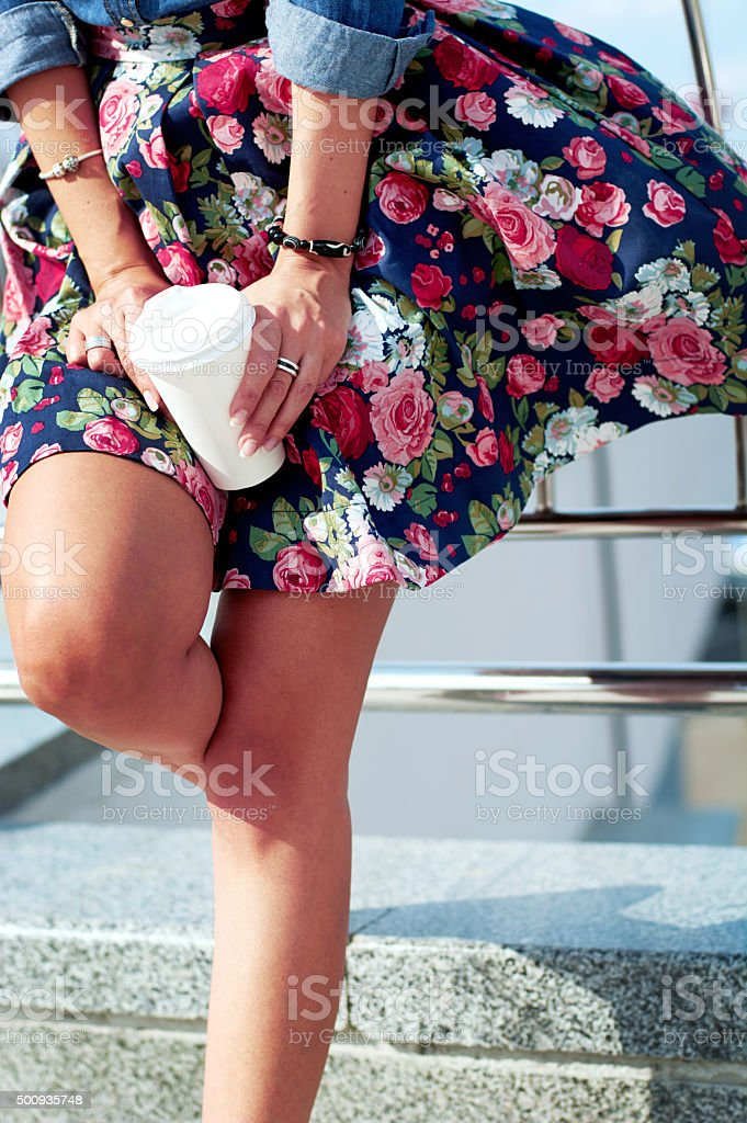The young woman with a cup of coffee in the city stock photo