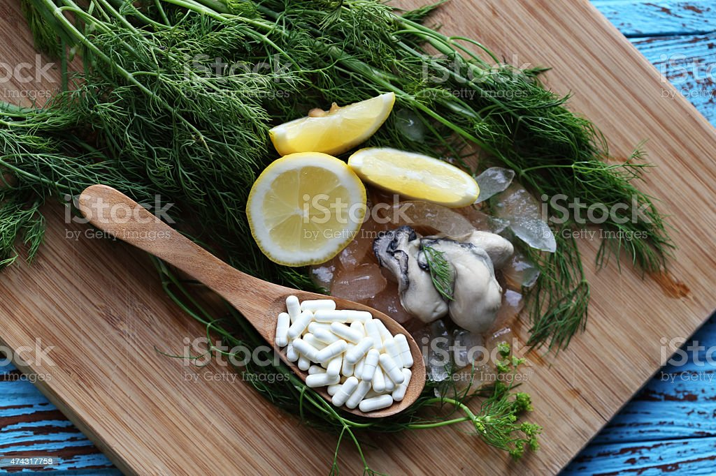The zinc supplementary white capsule with fresh oyster on block stock photo