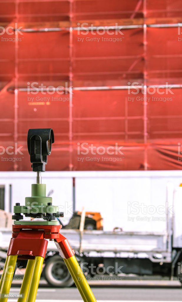 Theodolite building construction surveying equipment with scaffolding and safety netting in background - in Auckland, New Zealand, NZ stock photo