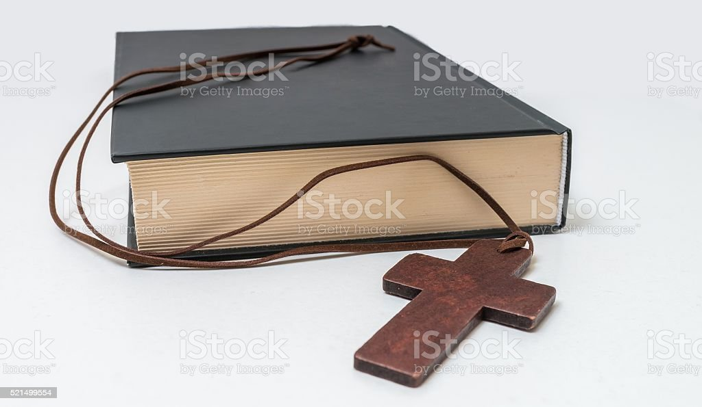 Theology concept. Bible book and brown crucifix on necklace. stock photo
