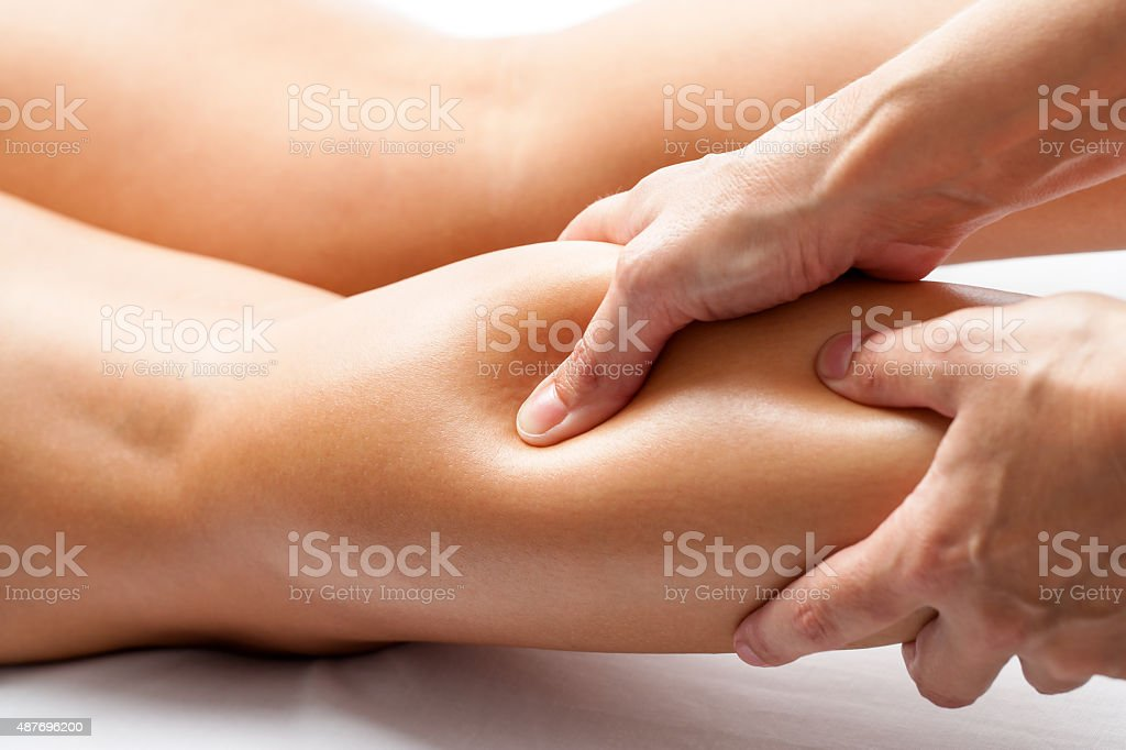 Therapist applying pressure with thumb on female calf muscle. stock photo