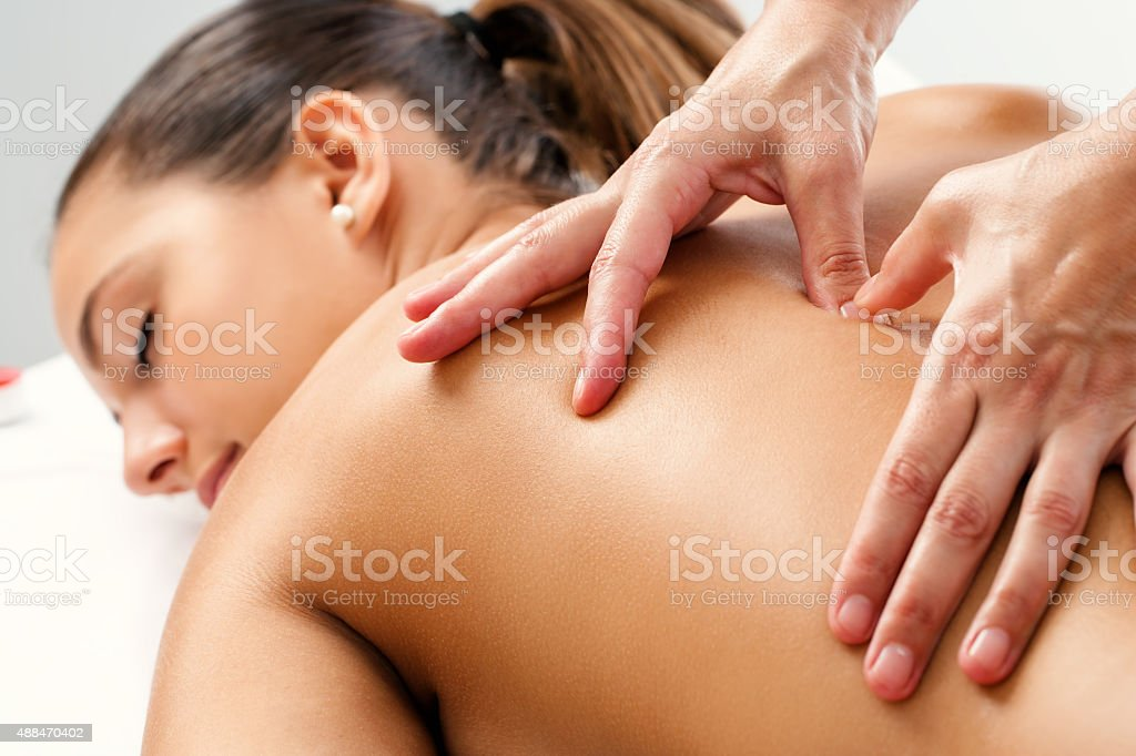 Therapist applying pressure with thumbs on back. stock photo